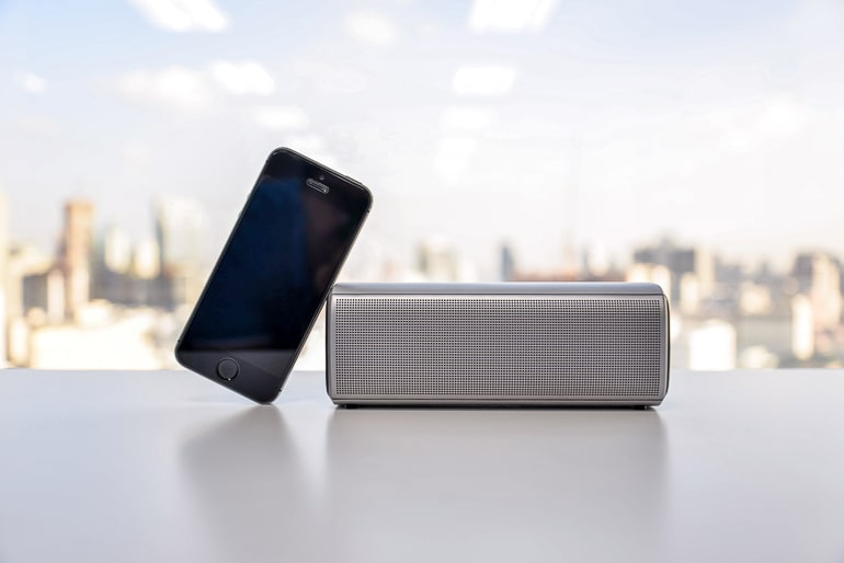 wireless speakers with black phone leaning on them and blurry skyline in background