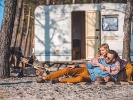 Couple hugging each other on ground in front of white trailer and trees couples bucket list