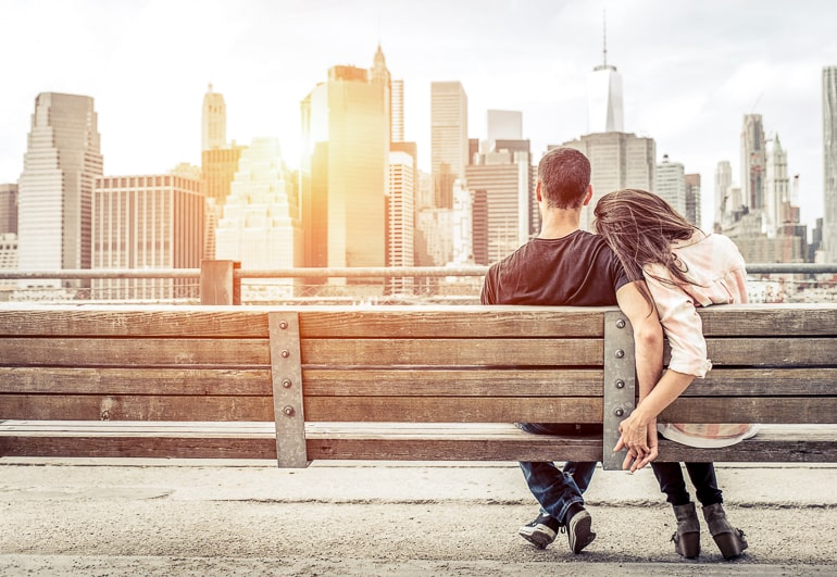 Couple sitting on park bench holding hands with city buildings in background