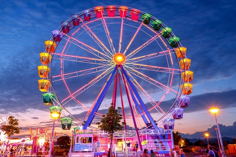 Colorful ferris wheel with dark blue sky in background