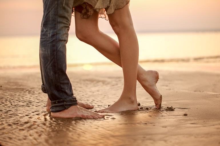 Legs of man and woman standing close to one another on sand
