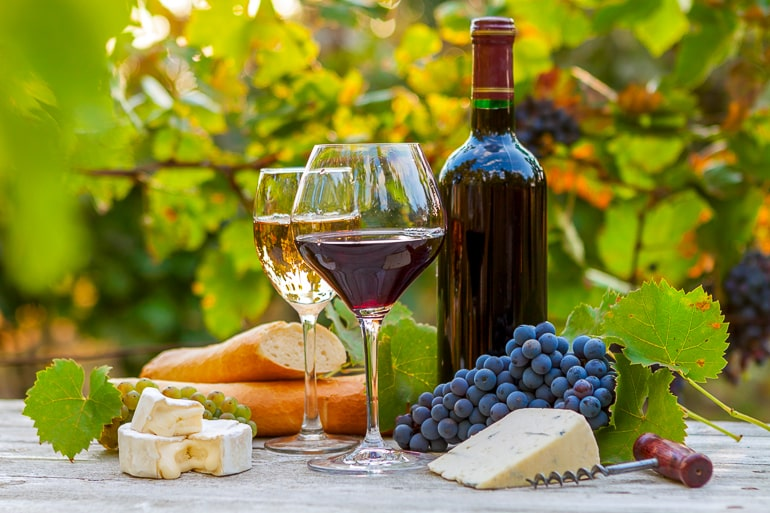 Glasses and bottle of wine with cheese bread and grapes on table