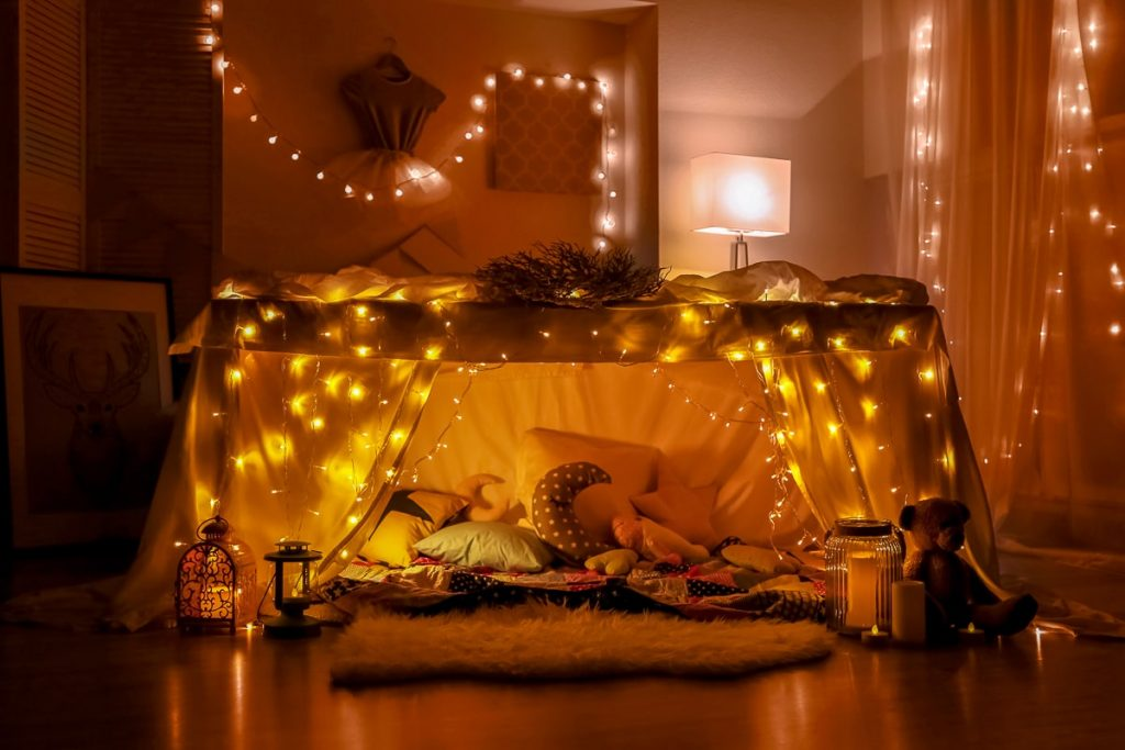 blanket fort in living room with fairy lights date night at home ideas