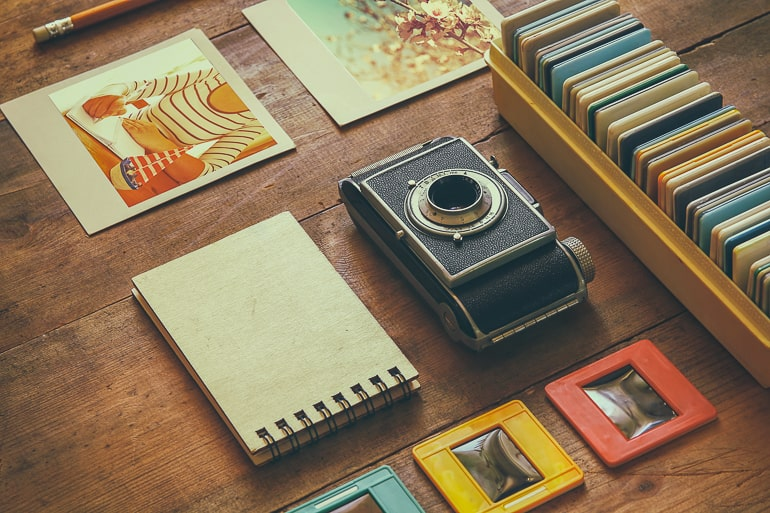 old camera and albums on wooden table date night at home ideas