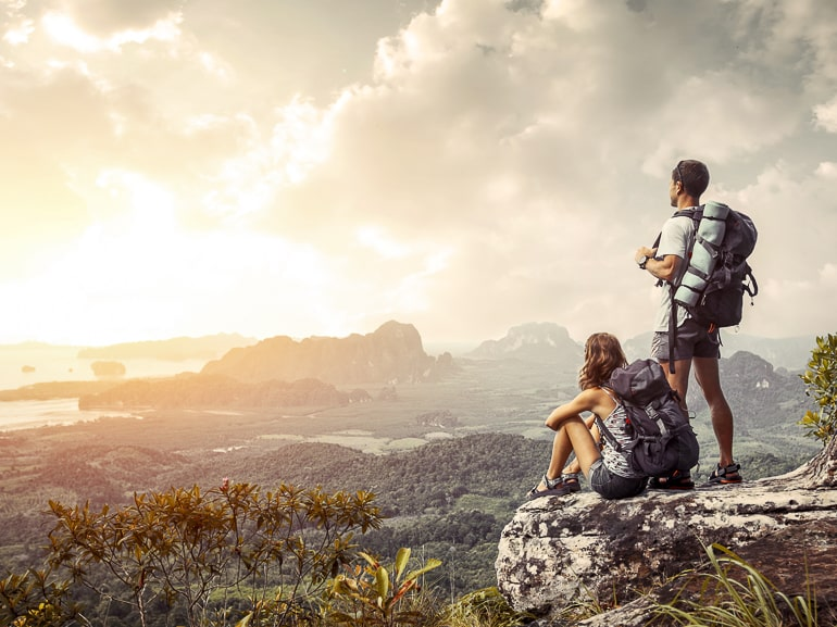 couple with backpacks standing on edge of cliff with sun and views