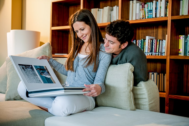 couple sitting in couch looking at photo album