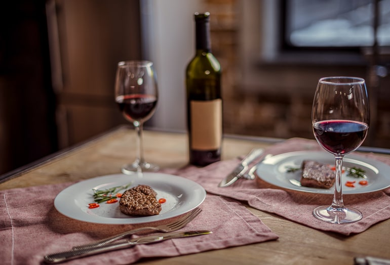 two plates with steak and wine glasses with bottle behind on table date night at home ideas