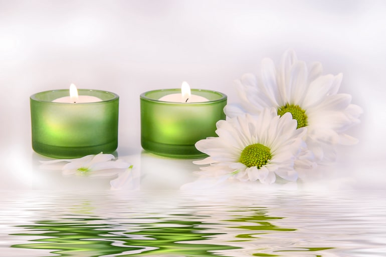 green candles with flowers and water in front spa night at home date ideas