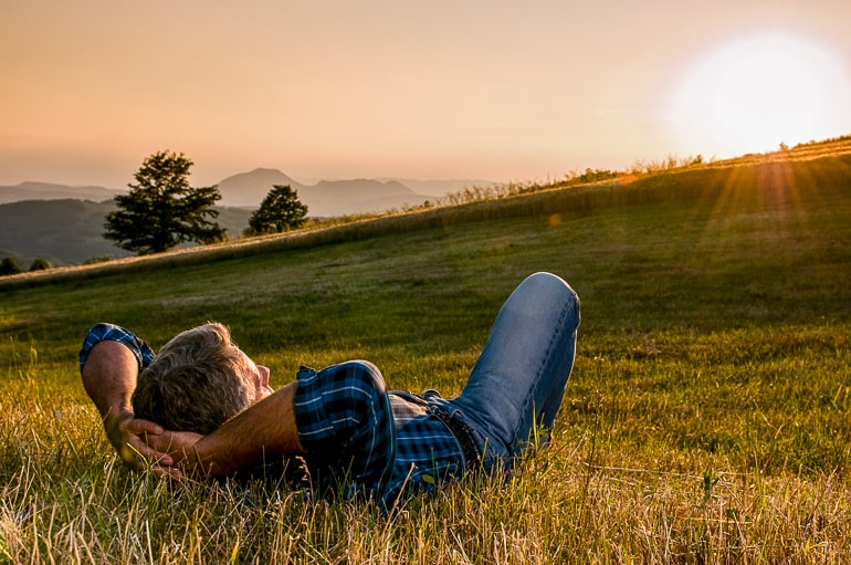 man laying in field looking at sunset introvert alone time