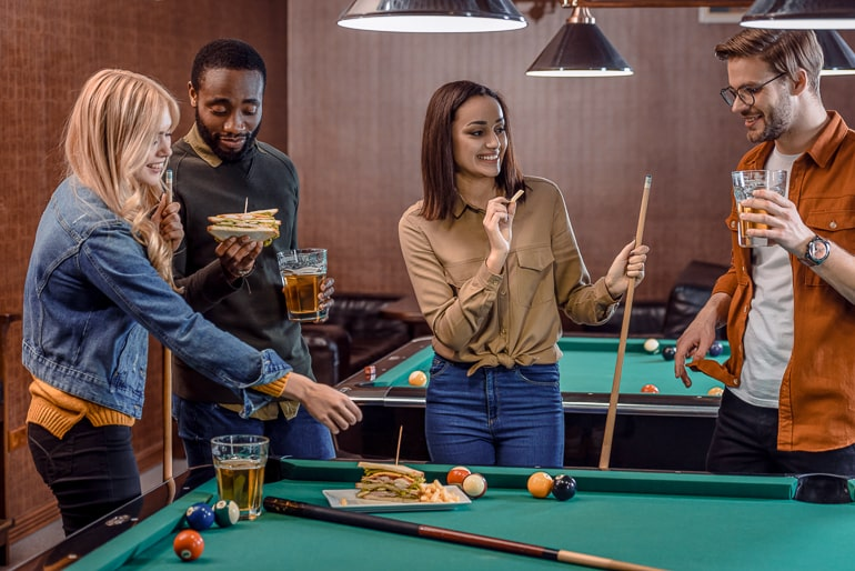 group of friends playing pool behind pool table