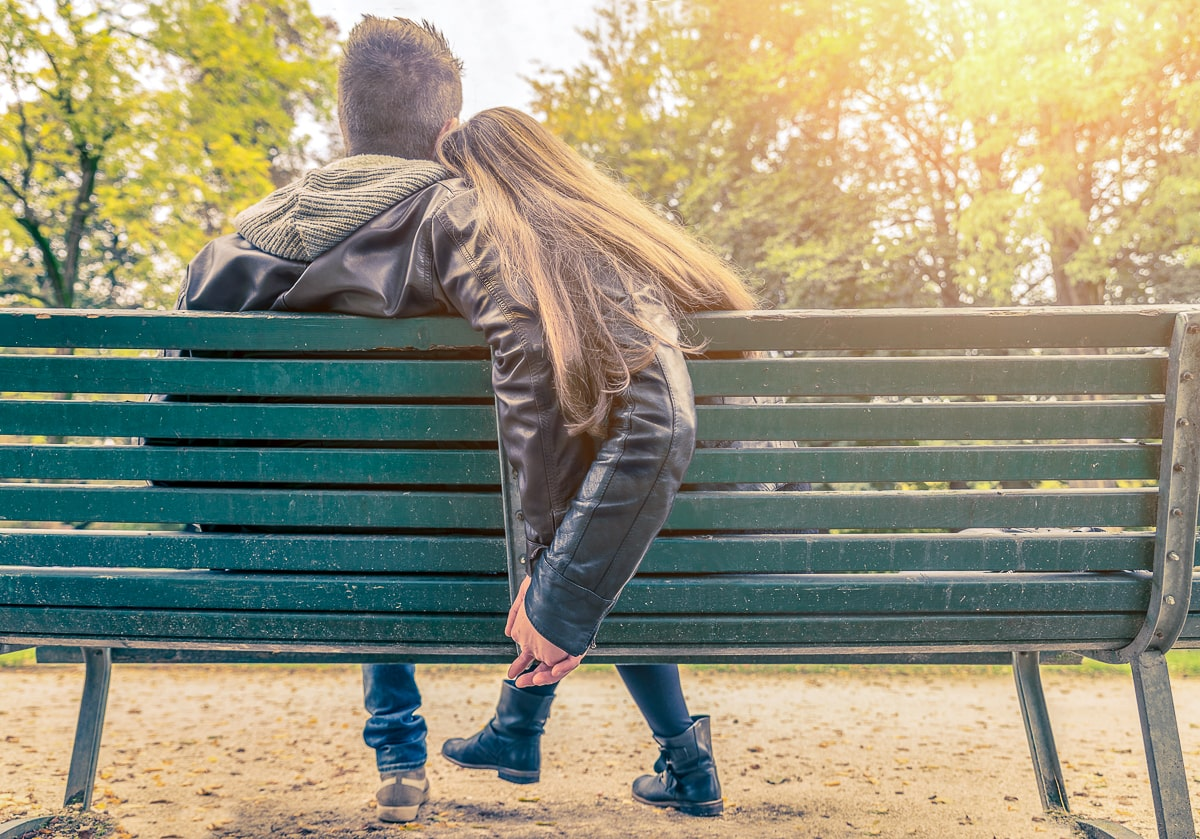 couple sitting in green bench in park dating an introvert