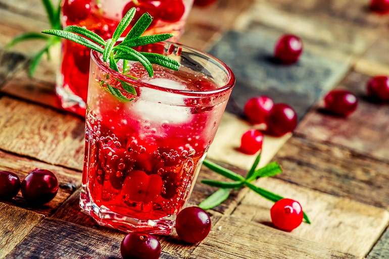 red vodka cranberry in short glass on wooden table top