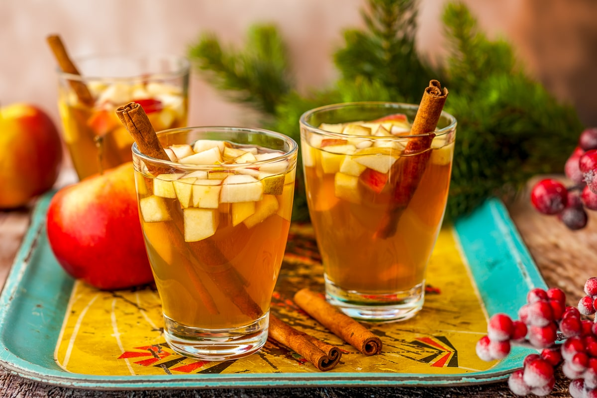 two mugs of apple cider with cinnamon sticks on tray of fall drinks