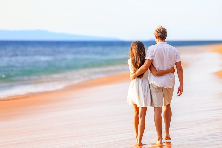 couple wearing white walking together down sandy beach