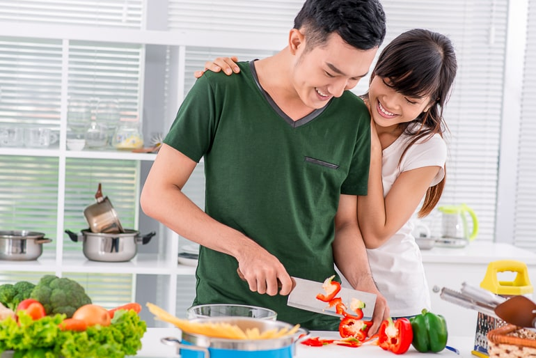 couple cooking together holding knife in kitchen