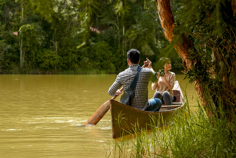 two people canoeing on brown river with tree in front