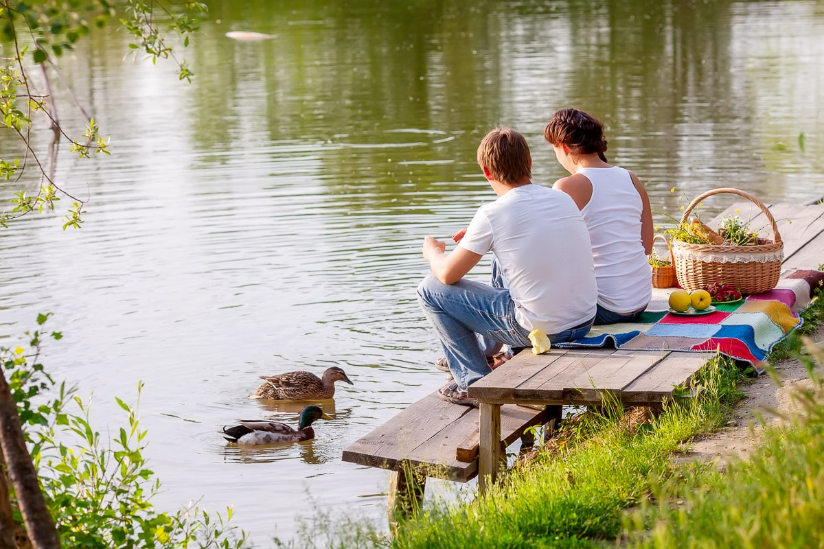 couple sitting in small dock by pond with food and ducks in water free inexpensive date ideas