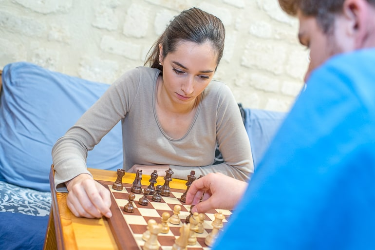 man and woman playing chess with blue couch behind free inexpensive date ideas