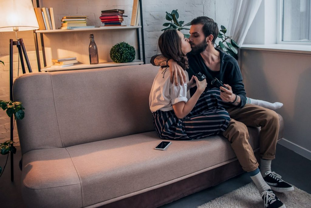 couple sitting in couch holding controllers while kissing