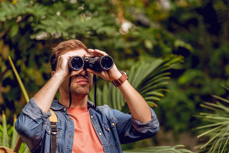 man standing looking through binoculars