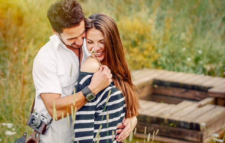 couple with flower and camera standing in field free inexpensive date ideas