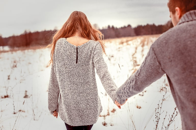 woman walking holding hand of man with snow on ground
