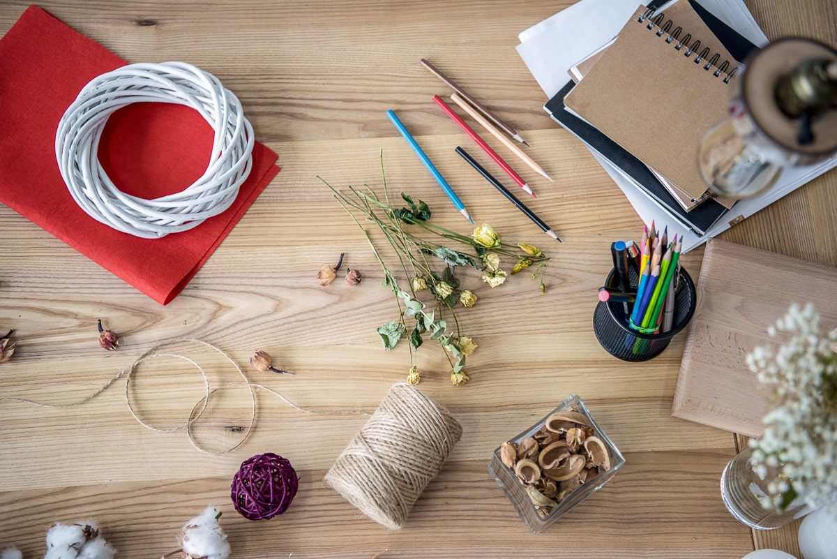 Pencils and twine and other craft supplies on wooden table frugal living tips