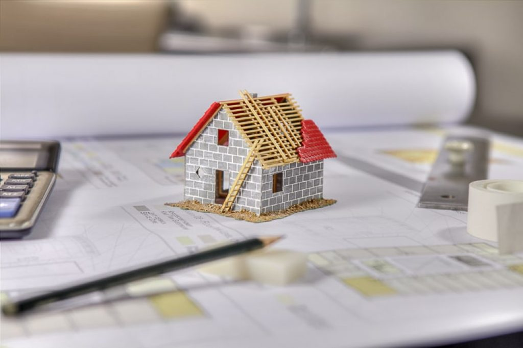 Tiny model of house on papers with calculator and pencil