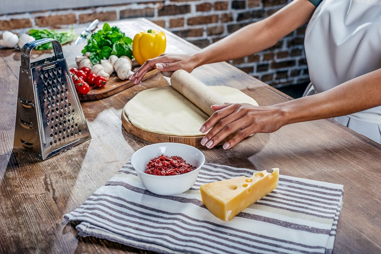 Person rolling out dough on wooden board with vegetables and cheese next to it