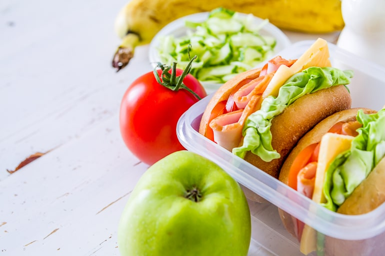 Lunchbox with sandwiches and apple tomato and banana next to it