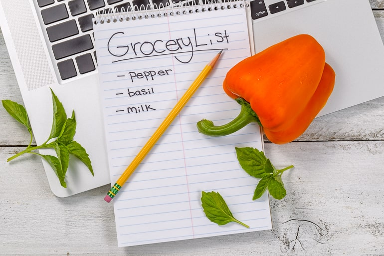 Orange pepper and pencil laying on top of grocery list and laptop