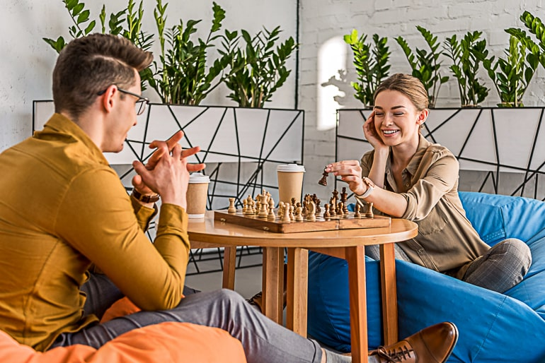 Man and woman sitting on beanbags and playing chess on small brown table