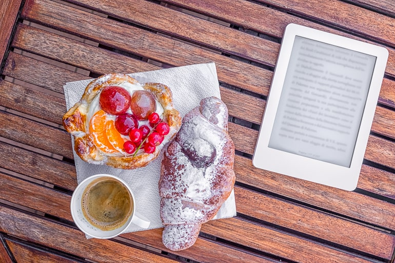 E Reader with mug of coffee and sweet pastries next to it on wood table mom gifts