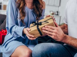 Woman in blue dress handing man sitting next to her a gift gifts for boyfriend for christmas