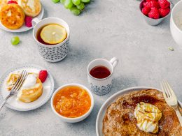 View of table with tea mugs and plates with pancakes and fruit gifts for foodies