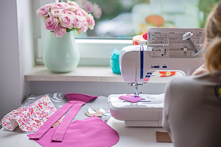 Woman sitting in front of sewing machine with fabrics next to it frugal gifts