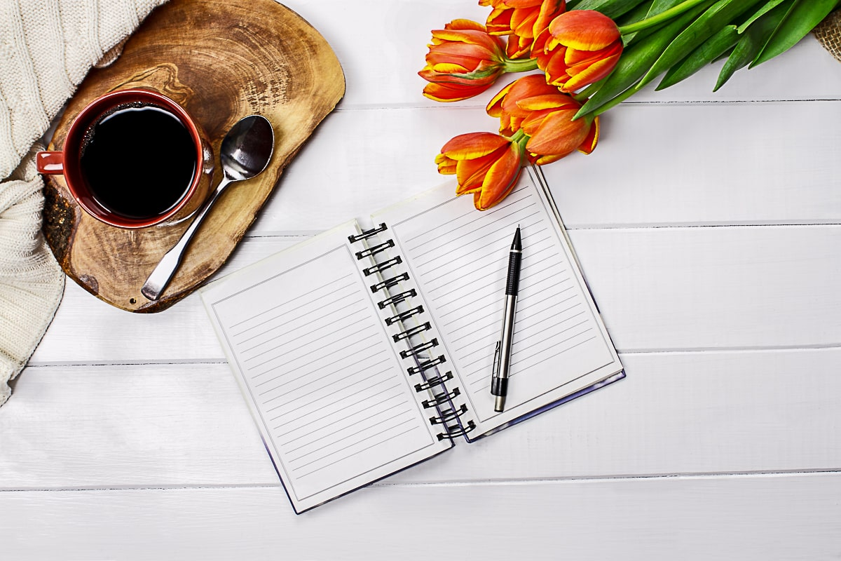 Open Journal with pen flowers and coffee mug on white background gifts for people with anxiety