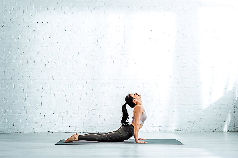 Woman doing yoga pose on black mat in front of white wall