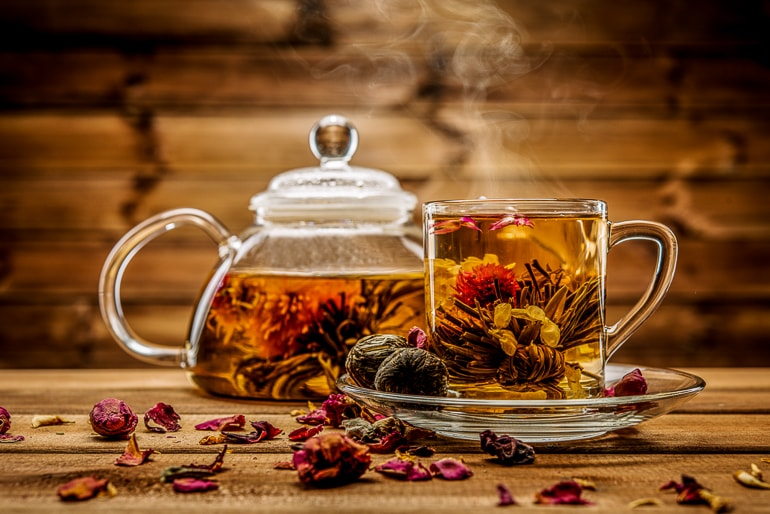 Glass tea pot and mug with tea and flowers in front of wood background
