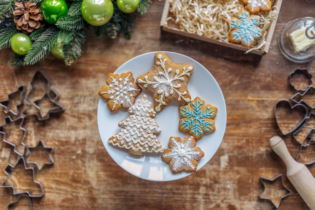 Decorated cookies on white plate on wood table with cookie cutters aroud it gift for bakers
