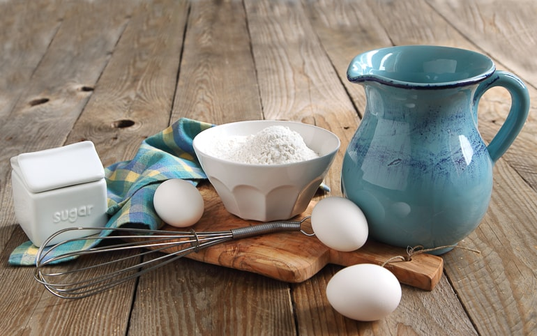 Blue jug and white mixing bowls with eggs and whisk on wood
