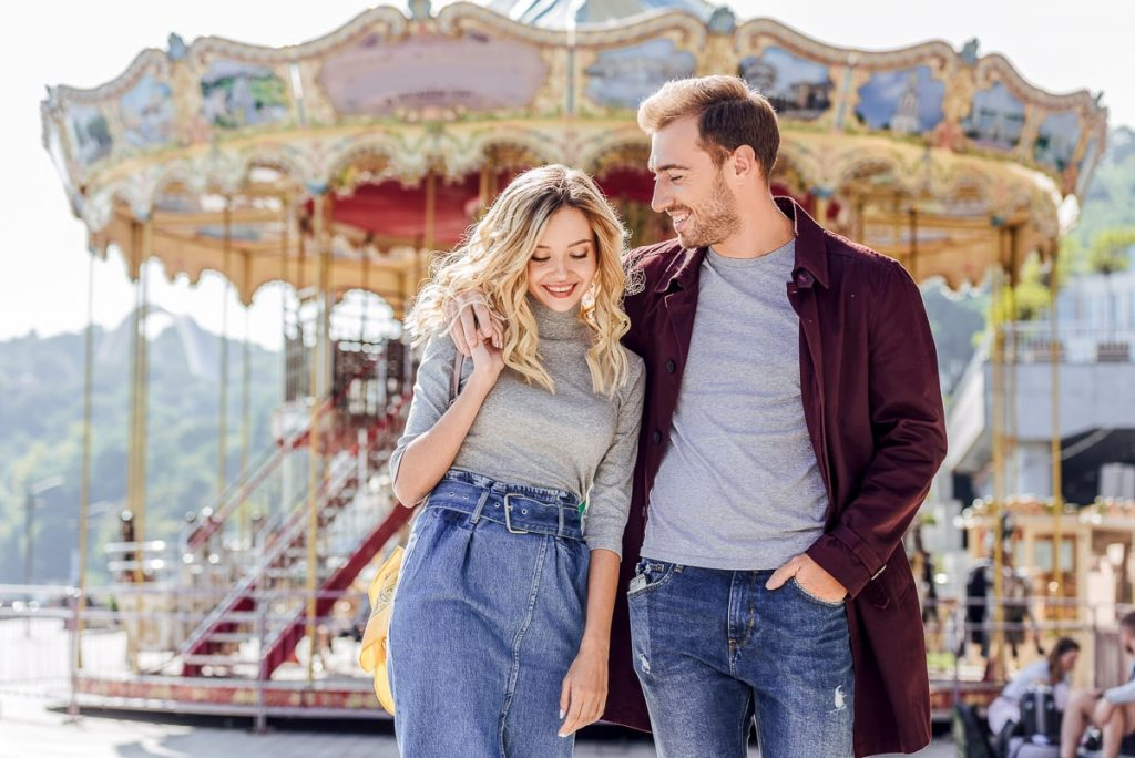 man and woman walking together in front of carousel good first date ideas