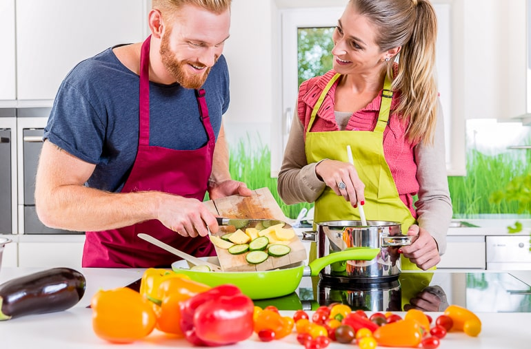 man and woman wearing aprons cooking together good first date ideas