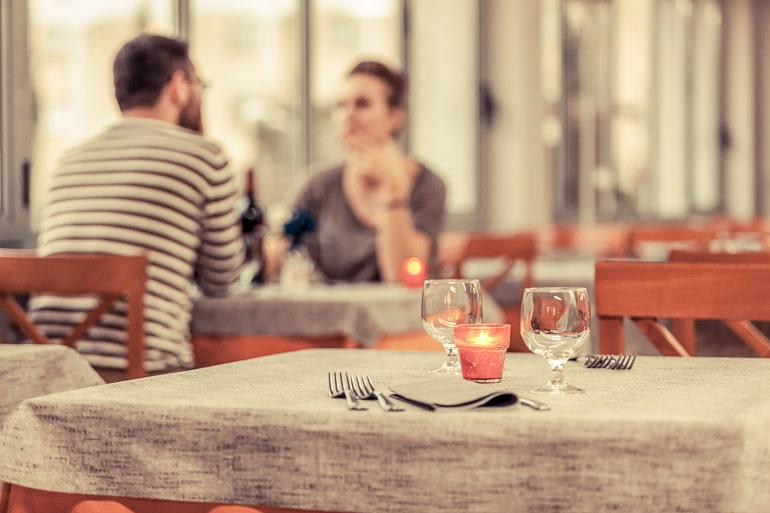 man and woman sitting at date table n distance with candle light
