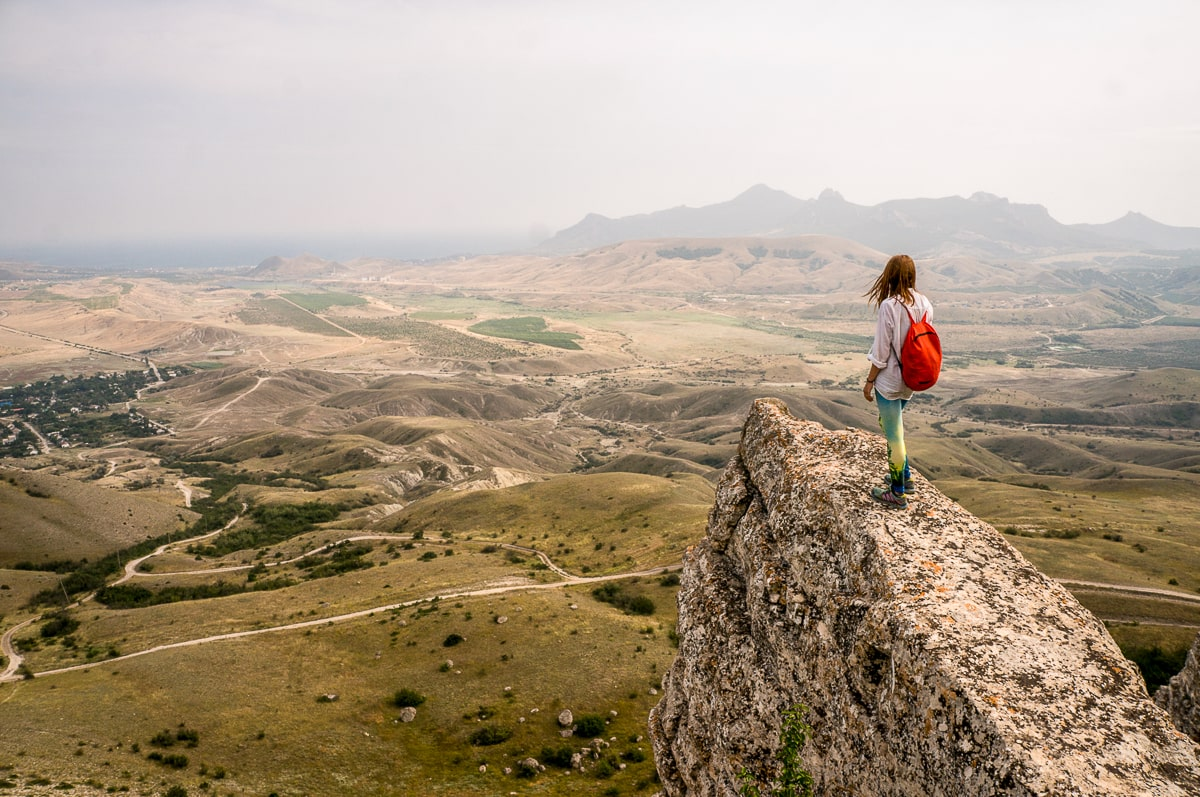 Woman with red backpack standing on big rock looking out over landscape growth mindset quote