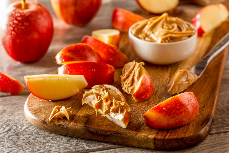 sliced apples with peanut butter on top on wooden board