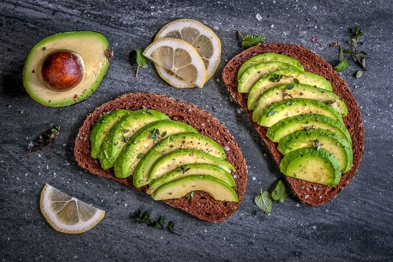 sliced avocado in dark rye bread