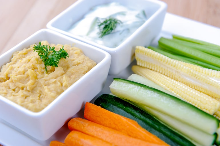 cut carrots and vegetables with dish of hummus healthy afternoon snacks