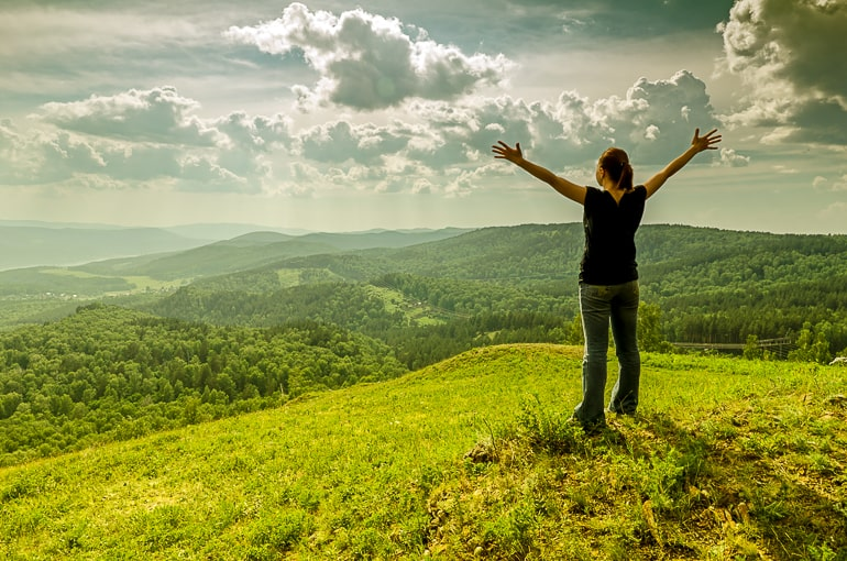 Woman standing on hill with raised arms and green forest in the background
