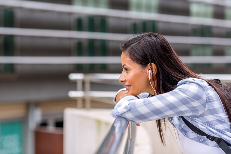 Woman with headphones leaning on railing and looking into distance healthy habits music